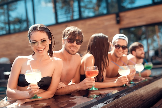 Young smiling friends with cocktails at poolside Premium Photo