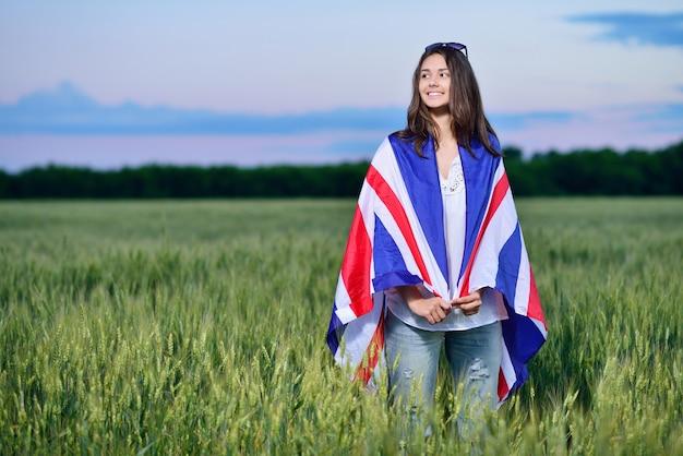 小麦畑で笑顔の少女。イギリスの旗。英語学習のコンセプト。 Premium写真