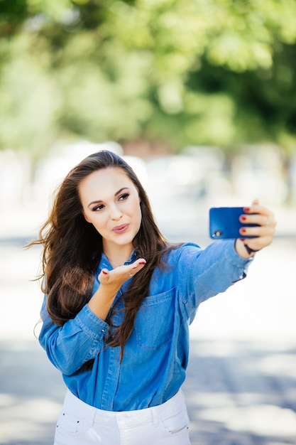 Young smiling girl making selfie send kisses on the background of the city Free Photo