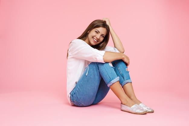 Молодая усмехаясь девушка сидя на поле обнимая колени смотря прямо Бесплатные Фотографии