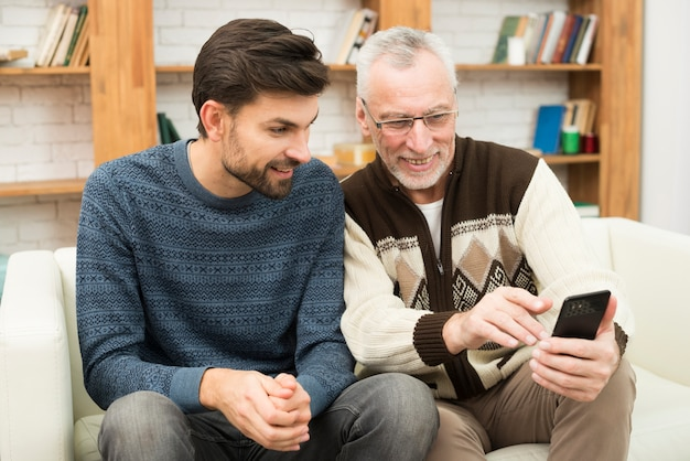 Young smiling guy and aged cheerful man using mobile phone on settee Free Photo