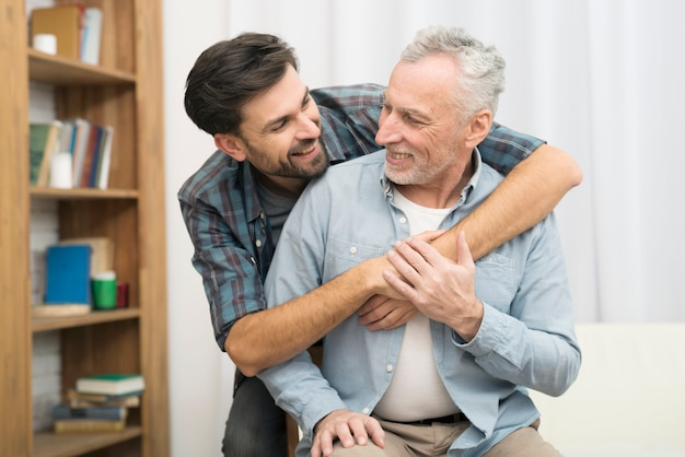 Young smiling guy hugging aged man Free Photo