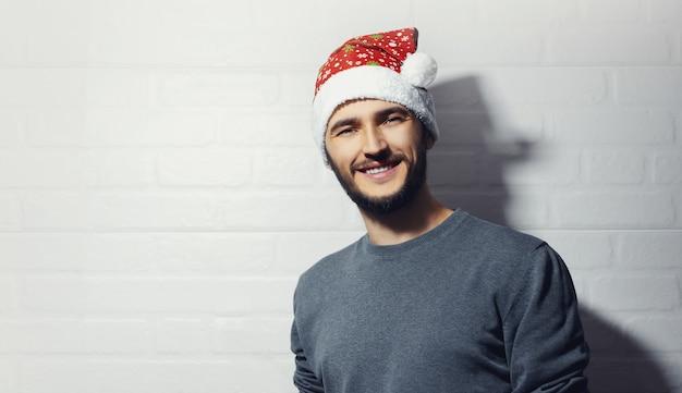 白いレンガの壁の背景に若い笑顔の男。クリスマスのコンセプト。 Premium写真