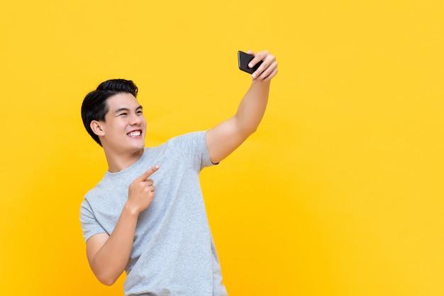 スマートフォンでselfieを取って笑顔若いハンサムなアジア人 Premium写真