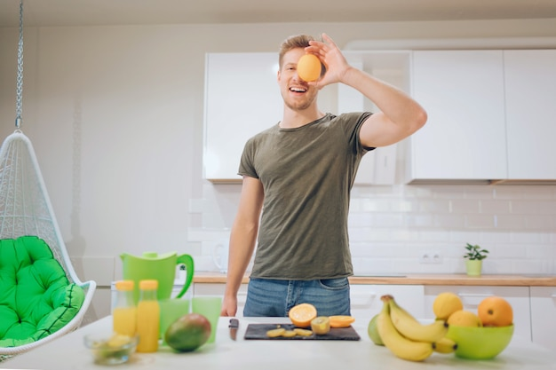 Молодой усмехаясь красивый человек держит сладкий апельсин перед лицом пока варящ свежие фрукты в кухне. Premium Фотографии