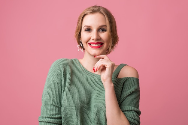 Young smiling happy attractive woman, red lips and nails polish, casual style, green sweater, cheerful, positive emotion, model posing in studio, isolated, pink background, looking in camera Free Photo