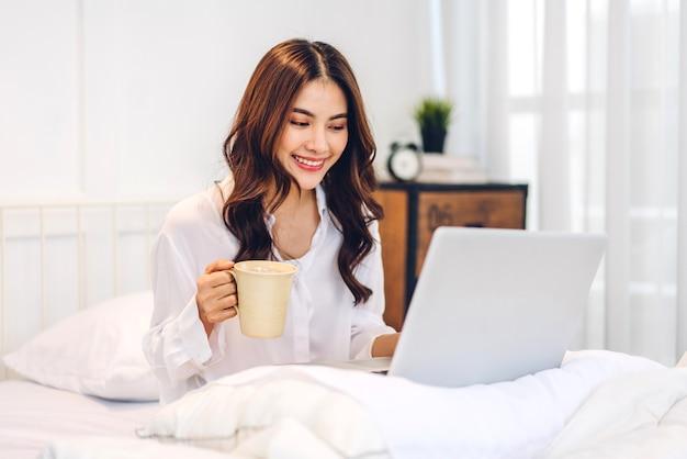 ラップトップコンピューターを使用してリラックスし、自宅の寝室でコーヒーを飲む若い笑顔の幸せな美しいアジアの女性。 Premium写真