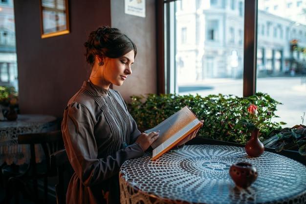 カフェで若い笑顔幸せな女 Premium写真