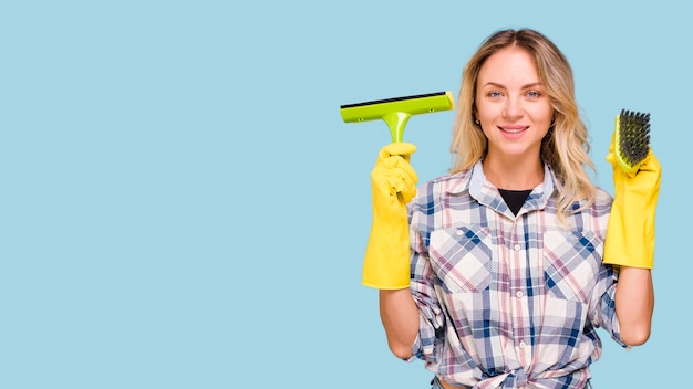 Young smiling housekeeper holding plastic wiper and brush standing against blue surface looking at camera Free Photo