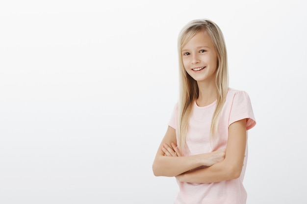Giovane ragazzo sorridente che sembra felice. piccola donna in piedi sul muro bianco allegro Foto Gratuite