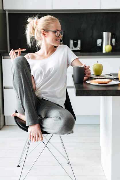 Young smiling lady looking aside while have breakfast in kitchen Free Photo