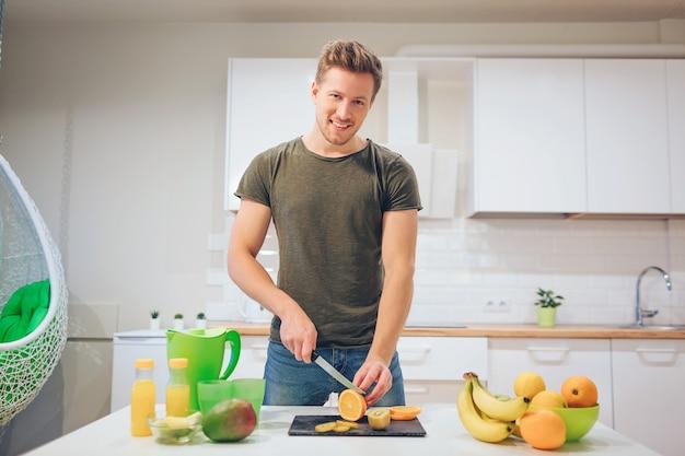 Молодой улыбающийся человек, приготовление свежих фруктов на кухне. здоровая пища. вегетарианская еда. диета детокс Premium Фотографии