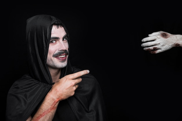 Young smiling man in halloween costume pointing at corpse hand Free Photo
