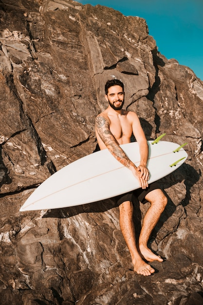 Young smiling man holding surf board near stones Free Photo