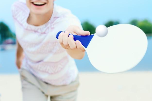 軽い服を着た若い笑みを浮かべて男は手に白いマコットラケットでボールを蹴っています。 Premium写真