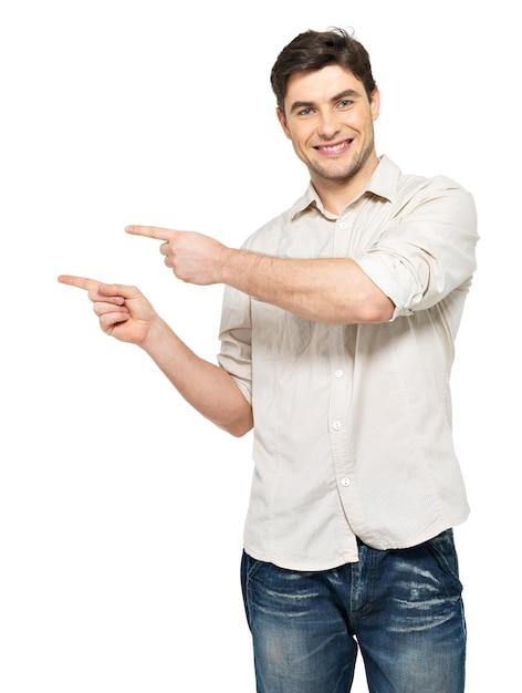 흰 벽에 고립 된 오른쪽에 손가락으로 젊은 웃는 남자 포인트. 무료 사진