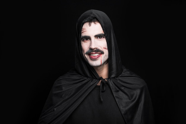 Young smiling man posing in black halloween costume Free Photo