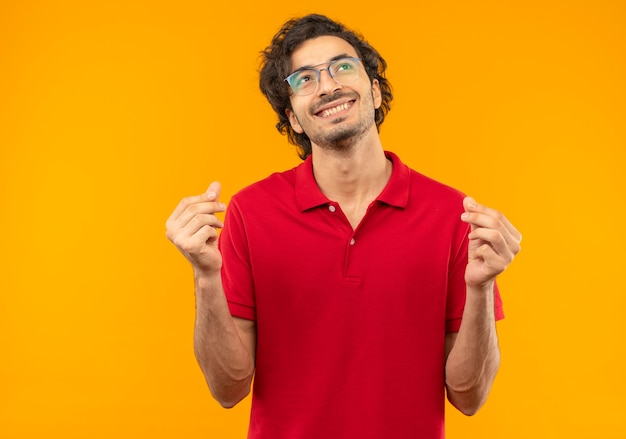 Young smiling man in red shirt with optical glasses gestures money with hands isolated on orange wall Free Photo