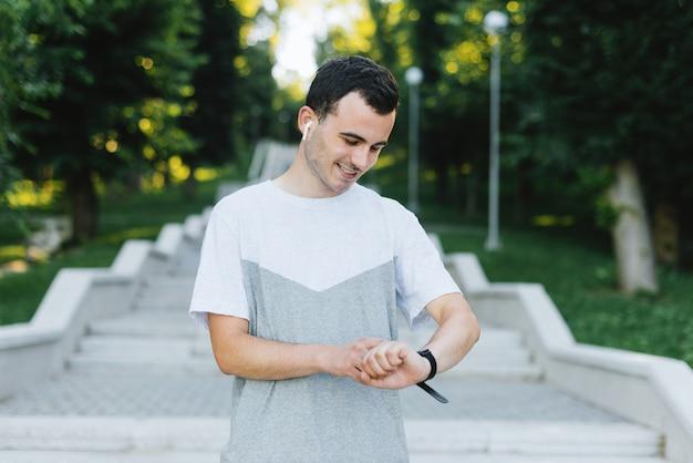 若い笑顔の男がワークアウトの前にフィットネスバンドのスマートな時計を設定したり、公園や屋外でその後チェックアウトしたりします。 Premium写真
