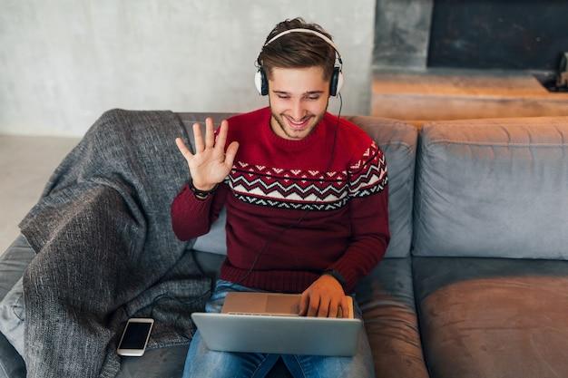 Giovane uomo sorridente seduto a casa in inverno, conversando online, agitando la mano, salutando, indossando un maglione rosso, lavorando al laptop, libero professionista, ascoltando le cuffie, studiando online Foto Gratuite