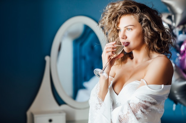 Young, smiling model  with a long curly  hair celebrating  married with champagne. Premium Photo