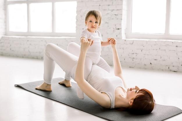 젊은 웃는 어머니 체육관에서 요가 운동을 하 고 재미있는 작은 딸과 함께 흰색 운동복을 입고, 아기, 재미와 스포츠 연습 활동을 즐기는 프리미엄 사진