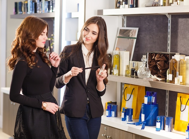 Young smiling positive saleswoman serving  customer in perfume shop. Premium Photo