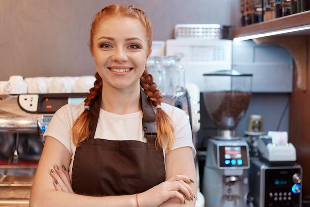 Giovane sorridente dai capelli rossi barista in piedi al bar nella caffetteria Foto Gratuite