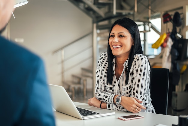 Young smiling saleswoman talking with a client. Premium Photo