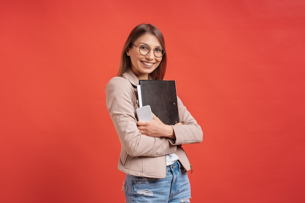 Young smiling student or intern in eyeglasses standing with a folder on red wall. Free Photo