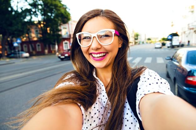 路上で自分撮りをする若い笑顔の十代の幸せな女性、髪の毛、明るいメイクとかわいい透明なメガネ、一人旅、楽しんで、前向きな気分、喜び、休暇 無料写真