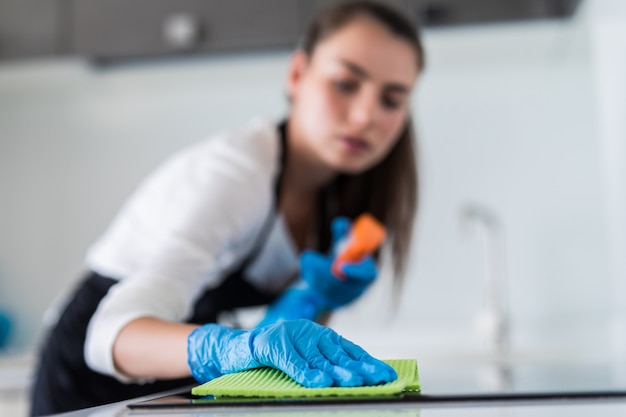 Young smiling woman cleans the kitchen at her home Free Photo