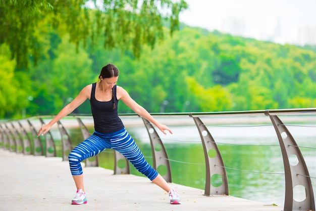 Young smiling woman doing sporty exercises outdoors Premium Photo