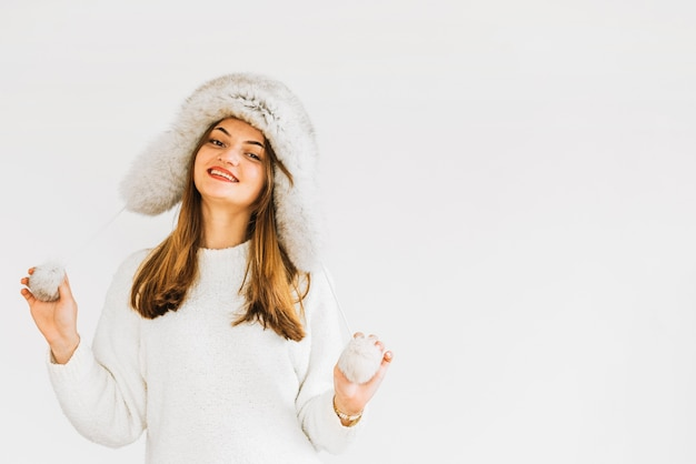 Young smiling woman in fur hat and sweater Free Photo