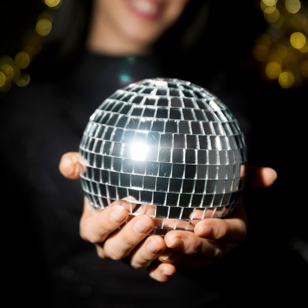 Young smiling woman holding disco ball Free Photo