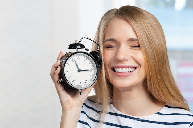 Young smiling woman holds black clock Premium Photo