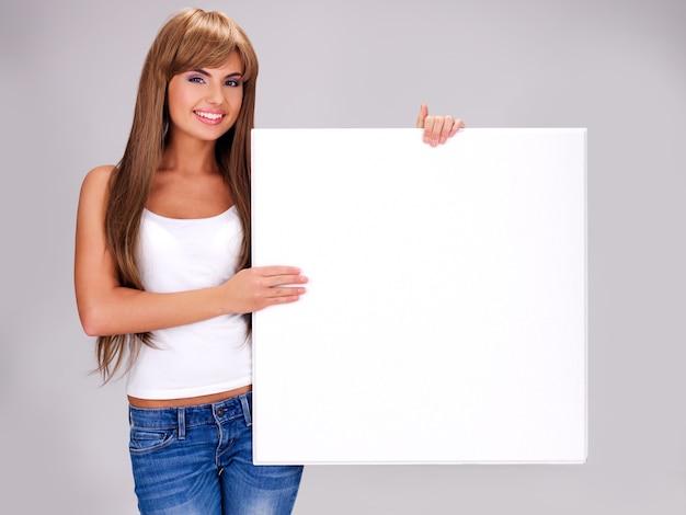 若い笑顔の女性は白い大きなバナーのポーズを保持します 無料写真
