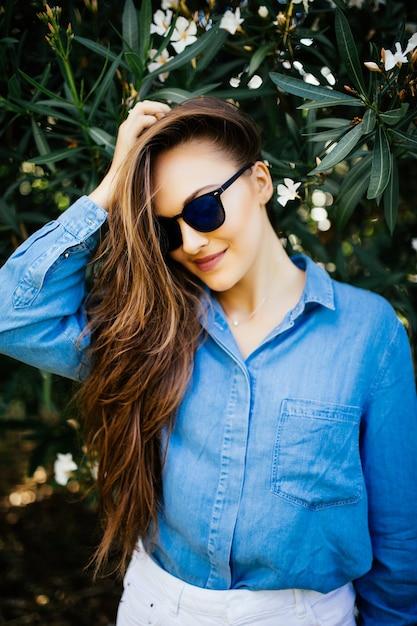 緑の自然な背景にサングラスで若い笑顔の女性。緑の葉の背景に女性の肖像画。 無料写真