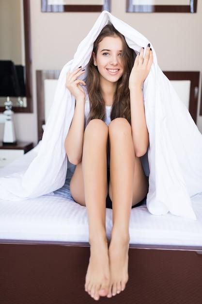 若い笑顔の女性は白い寝具、ホテルのコンサート、モダンなアパートメントでベッドで彼女の頭の上に毛布で座っています。 無料写真