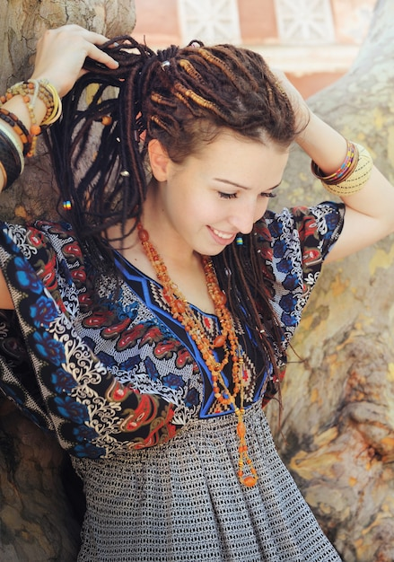 Young smiling woman portrait with dreadlocks dressed in boho style ornamental dress Premium Photo