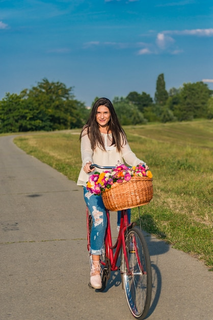 Premium Photo | Young smiling woman rides a bicycle with a basket full of  flowers in countryside