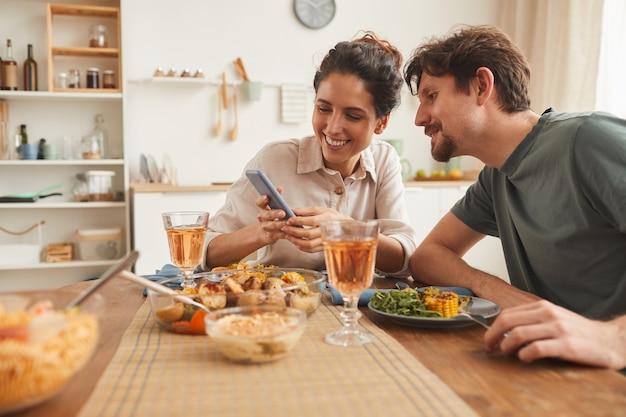 Молодая улыбающаяся женщина показывает фотографии на своем мобильном телефоне своему парню во время ужина на кухне дома Premium Фотографии