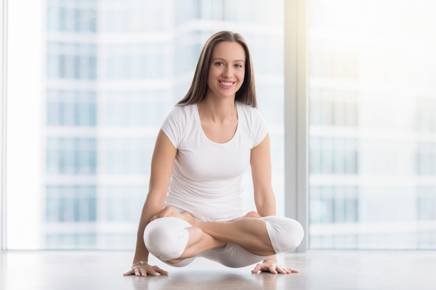 Young smiling woman in tolasana pose against floor window Free Photo