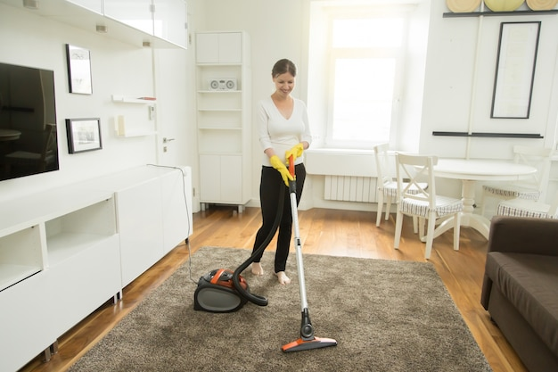 Young smiling woman vacuum cleaning the carpet Free Photo