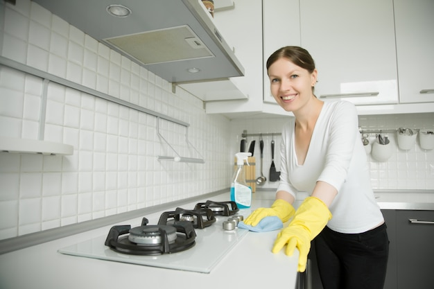 Young smiling woman wearing rubber gloves cleaning the stove Free Photo