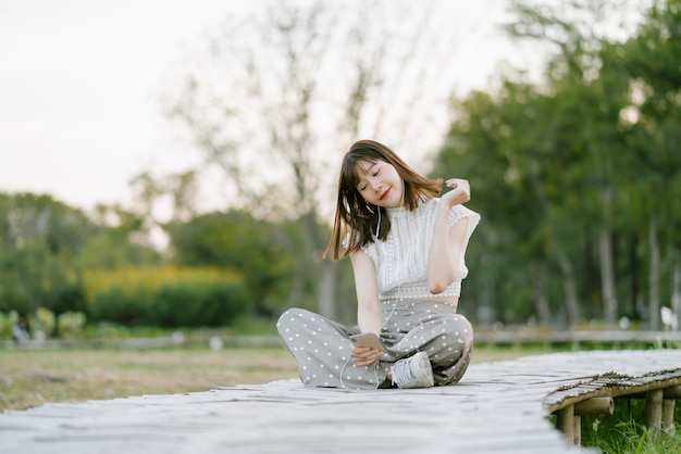 Young smiling woman in white clothes with earphones sitting on wooden walkway in the park and enjoying her moment while using mobile phone listening to music with her eyes looking at the screen Premium Photo