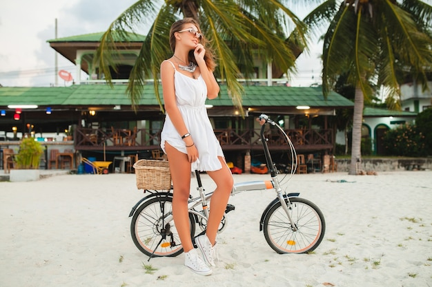 Giovane donna sorridente in abito bianco a cavallo sulla spiaggia tropicale su occhiali da sole in bicicletta che viaggiano in vacanza estiva in thailandia Foto Gratuite