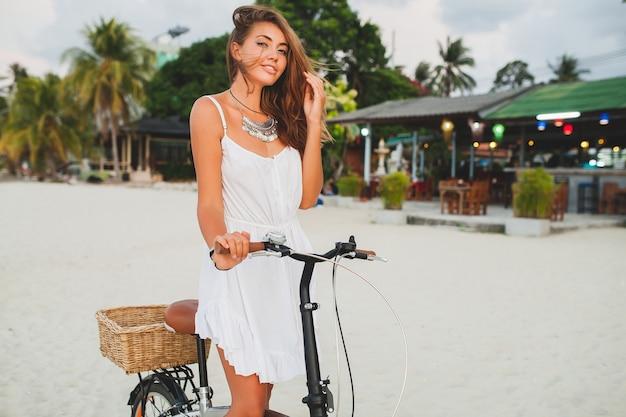 Giovane donna sorridente in abito bianco, camminando sulla spiaggia tropicale con la bicicletta che viaggia in vacanza estiva in thailandia Foto Gratuite