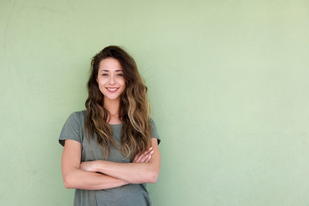 Young smiling woman with arms crossed against green background Premium Photo