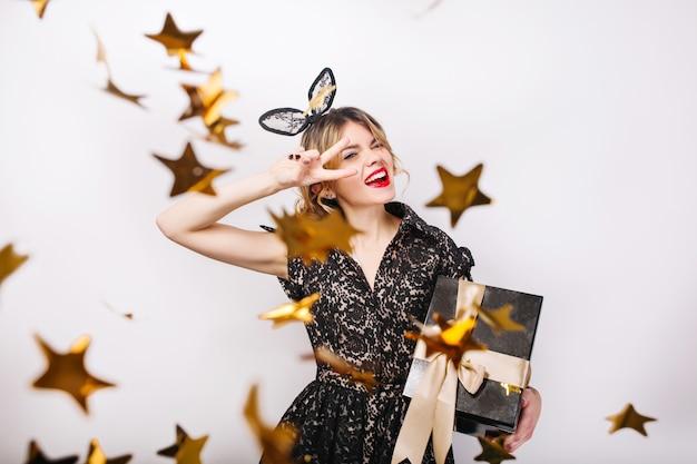 明るいイベント、誕生日パーティーを祝うギフトボックスを持つ若い笑顔の女性は、エレガントなファッションの黒のドレスを着ています。輝く金の紙吹雪、楽しんで、踊る。 無料写真